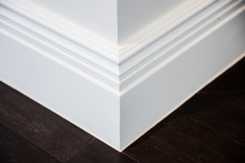 Ornamental Moulding In The Corner Of A White Room With Dark Wood Floor Interior Concept