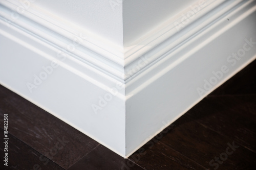 Ornamental moulding in the corner of a white room with dark wood floor interior Canvas Print