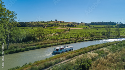 Cuadros en Lienzo Aerial top view of boat in Canal du Midi from above, family travel by barge and