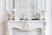 White Mantelpiece With Candles And Christmas Decorations. Classic Interior.