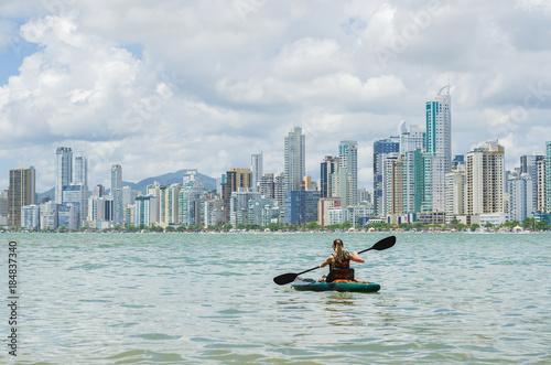 Fototapeta Jovem mulher loira passeando de caiaque em praia do brasil com prédios no fundo,