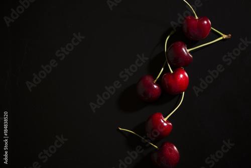 Fotografija Raw cherries on black background