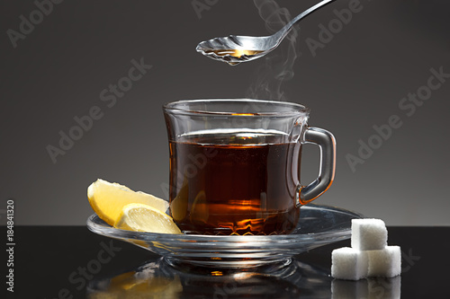 Staande foto Thee Spoon above cup of hot tea.