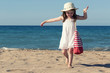 Little girl in white dress walking alone the sea, playing on the seashore