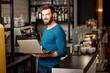 canvas print picture - Handsome man in blue sweater working with laptop at the bar of the modern cafe interior