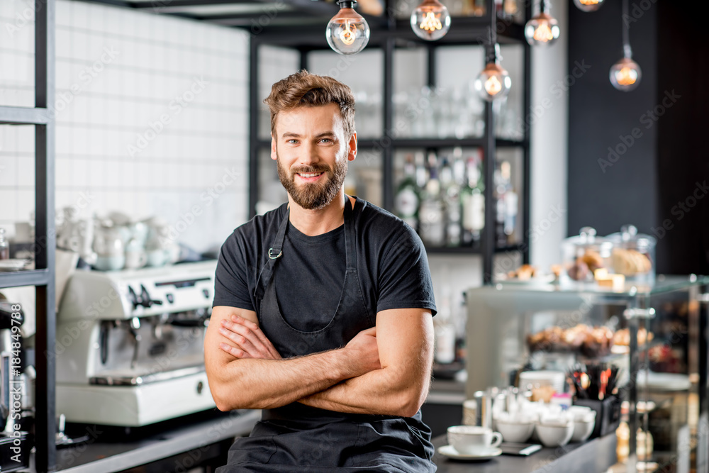 Fototapeta Portrait of a handsome barista in black t-shirt and apron sitting at the bar of the modern cafe