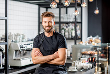 Portrait Of A Handsome Barista In Black T-shirt And Apron Sitting At The Bar Of The Modern Cafe