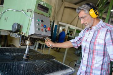 Man using industrial machine, wearing earmuffs