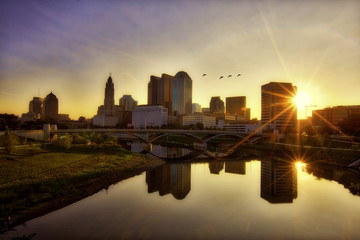 Sunrise along the Scioto river with birds flying over the Columbus, Ohio skyline