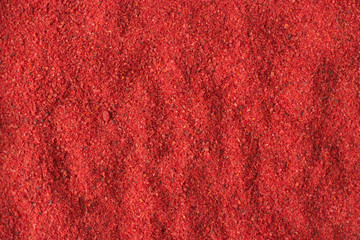 Fototapetahot chili pepper powder spice as a background, natural seasoning texture
