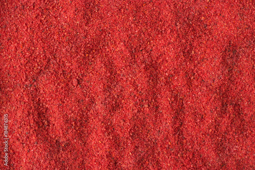 Tuinposter Hot chili peppers hot chili pepper powder spice as a background, natural seasoning texture