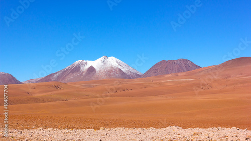 Foto op Aluminium Oranje eclat Natural beauty of unspoiled desert landscape. Colorful landscape of rocks, sandy valleys, and volcanic mountains with snow peaks in Atacama Desert, Chile.