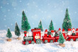 Red Christmas toy train with fir trees and snowfall.