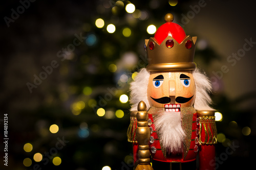 Fotomural Christmas nutcracker with Christmas tree and lights in background