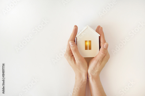 Obraz The model of the White House with warm light inside in female hands on a white background - fototapety do salonu