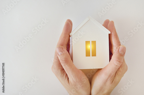 Fotografía The model of the White House with warm light inside in female hands on a white b