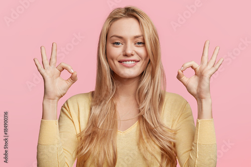 Fotografía  Glad attractive woman shows ok sign as expresses approval, gestures in studio against pink background, has cheerful expression