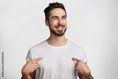 Fotografía  Glad positive male with beard and mustache wears casual white t shirt, has shining happy eyes and pleasant broad smile, indicates at copy space for your design