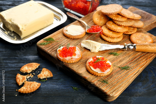 Crackers with butter and red caviar on wooden board