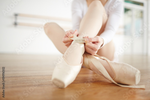 Ballerina sitting on the floor of classroom and tying white satin ribbons around her ankles