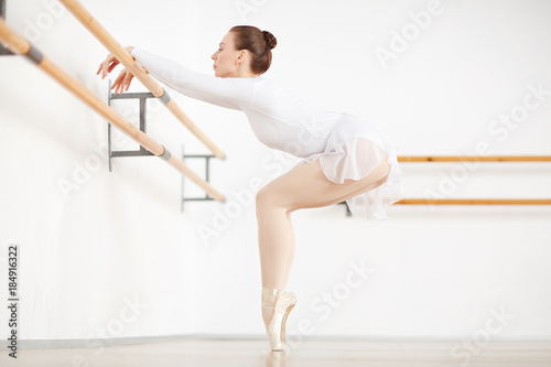 Ballerina standing on tiptoes with her legs put together and bent knees while keeping hands on bar