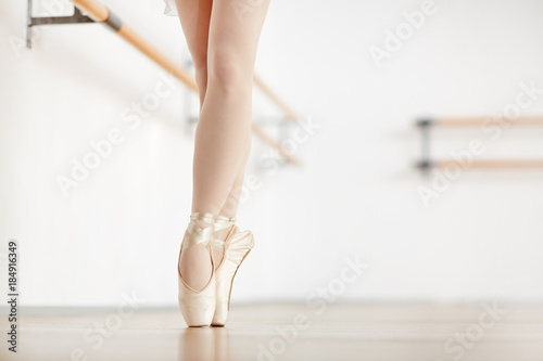 Tiptoe stand of ballerina in satin points during training in class