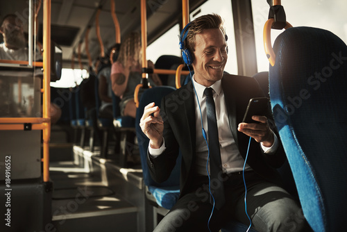 Young businessman sitting on a bus listening to music - 184916552
