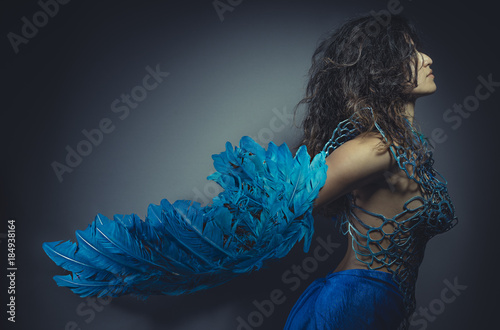 beautiful brunette girl in a suit made of blue wires, bears bird wings and color Fototapet