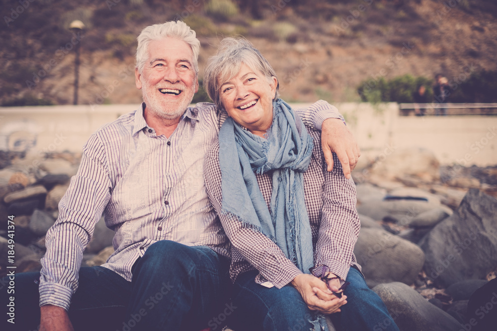 Fototapeta gentlemen couple sitting at the beach at sunset. smile and happy lifestyle for aged mature caucasian people in outdoor leisure activity. hug and love forever