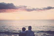 Gentlemen Couple Sitting At The Beach At Sunset