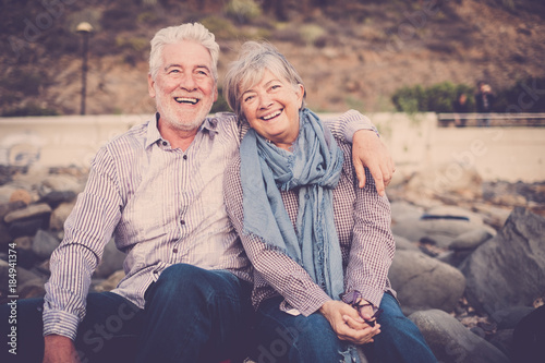 gentlemen couple sitting at the beach at sunset. smile and happy lifestyle for aged mature caucasian people in outdoor leisure activity. hug and love forever