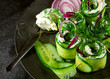 Cucumber rolls with cream cheese, dill and onions decorated on a plate