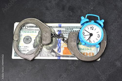 Photo Handcuffs, money and alarm clock on dark background, bail concept