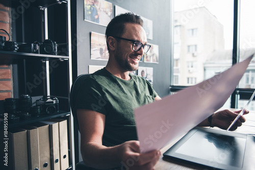 Fototapety, obrazy: Side view outgoing unshaven man watching at photos while sitting at desk in office. Occupation concept