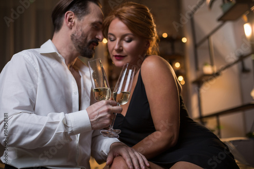 Ingelijste posters Dance School Passionate mature man is touching female leg with desire while holding glasses of champagne. Focus on drink