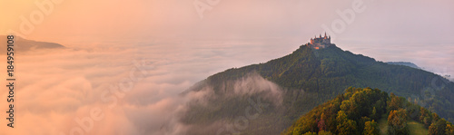 German Castle Burg Hohenzollern over the clouds at sunset landscape Wallpaper Mural
