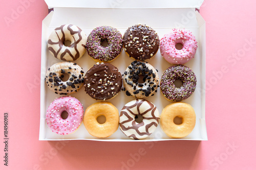 Photo Box of fancy donuts with sprinkles on pink background