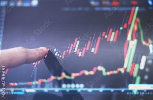 Fotografía  Finger pointing on stock exchange market chart, raising graph
