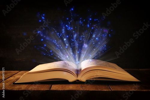 Fototapety, obrazy: image of open antique book on wooden table with glitter overlay.