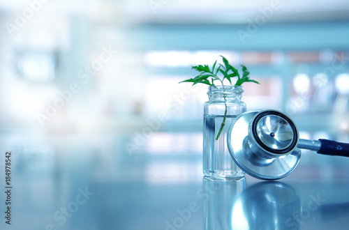 Fotografia  stethoscope for medical doctor diagnosis with vial glass and green leave plant i