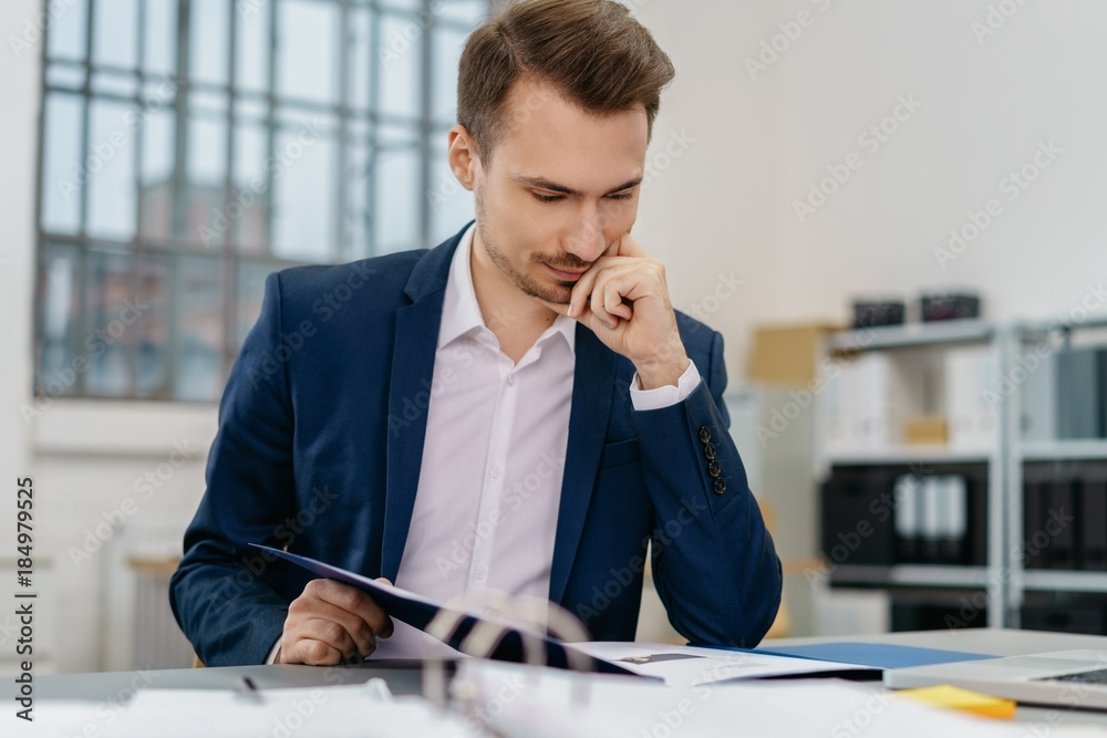 Fototapeta Young man reading files at desk in office