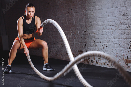 Photographie  Woman training with battle rope in cross fit gym