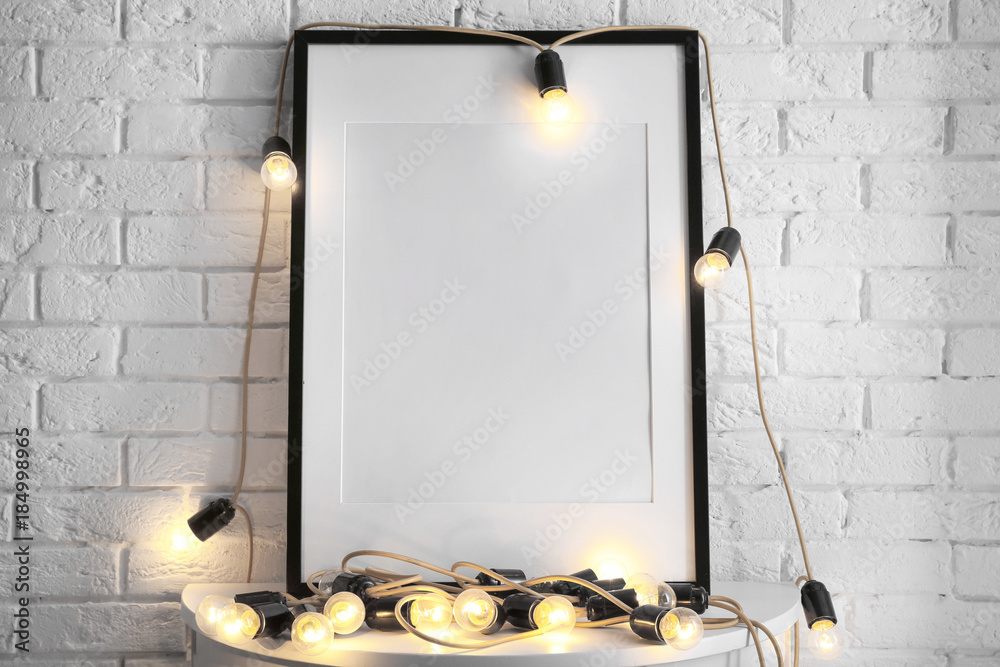 Fototapety, obrazy: Mockup of blank frame with garland on table