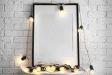 Fototapeta Bambus - Mockup of blank frame with garland on table