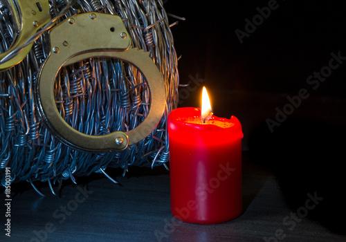 Photo eine rote Kerze leuchtet vor Stacheldraht und Handschellen