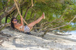 young beautiful Chinese Asian girl having fun on beach tree swing enjoying happy feeling free in Summer holiday tropical trip