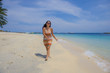 beautiful Chinese Asian girl in Summer dress walking on beach sand with amazing beautiful turquoise sea water color enjoying holidays relaxed