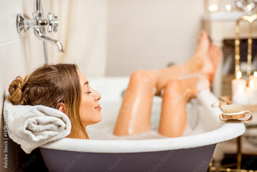 Fototapeta Young woman relaxing in the beautiful vintage bath full of foam in the retro bathroom decorated with candles