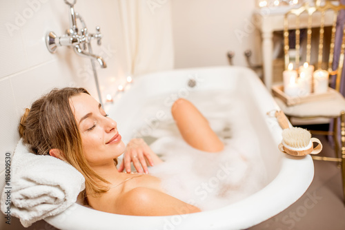 Young woman relaxing in the beautiful vintage bath full of foam in the retro bat Fotobehang