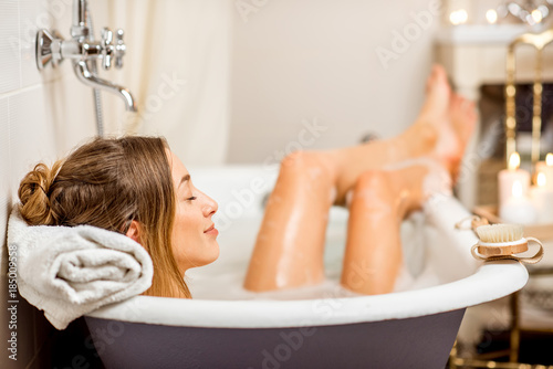Young woman relaxing in the beautiful vintage bath full of foam in the retro bat Fototapete